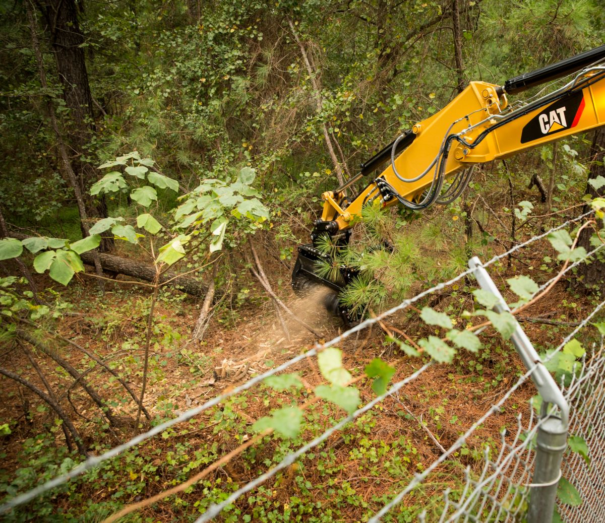 Cat® HM210 Mulcher Clearing Brush on Over a Fence