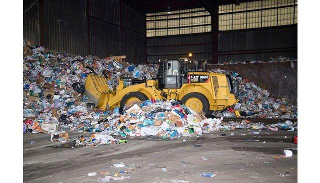 966M XE Waste Handler moving solid waste and saving fuel in a Transfer Station.