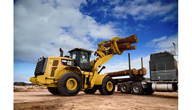962M Logger with Cat Millyard Forks unloading a truck in a saw mill