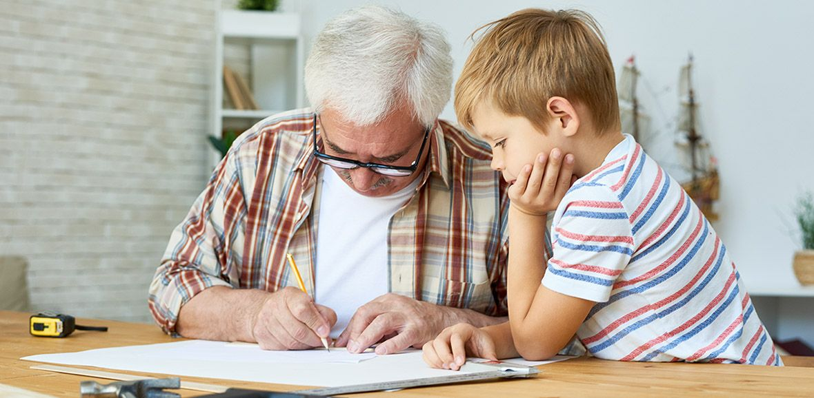 Older man and young boy looking at paperwork on a desk