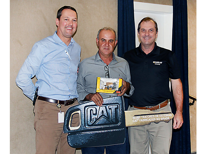 Customer Carlos Travensollo receives the commemorative key from Earthmoving Vice President Frédéric Istas and Brazil Country Manager Odair Renosto