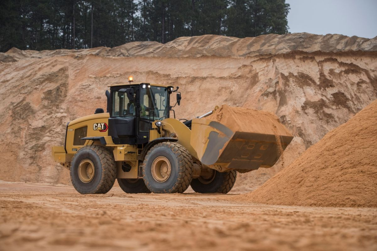 person performing maintenance on a small wheel loader