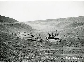 Cat machines help construct the Kainji Dam in Nigeria, 1964.