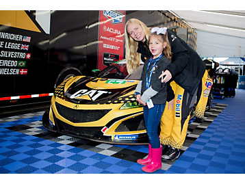 A young fan poses with No. 57 IMSA driver Christina Nielsen.