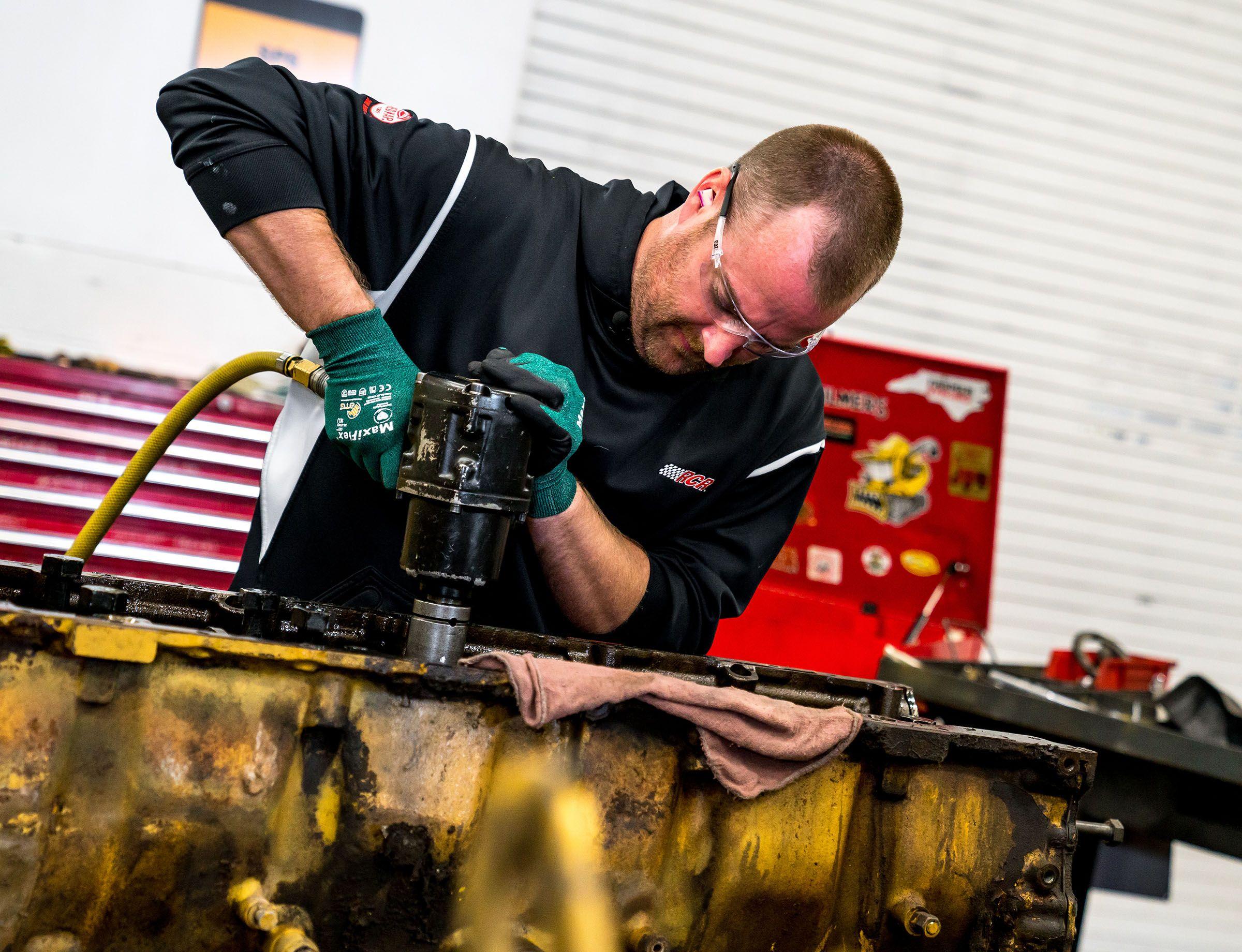 RCR technician Blake Zobrist helps remove a crankshaft from a C18 engine.