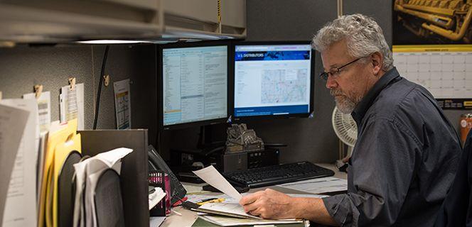 Man Looking at Paperwork at his desk