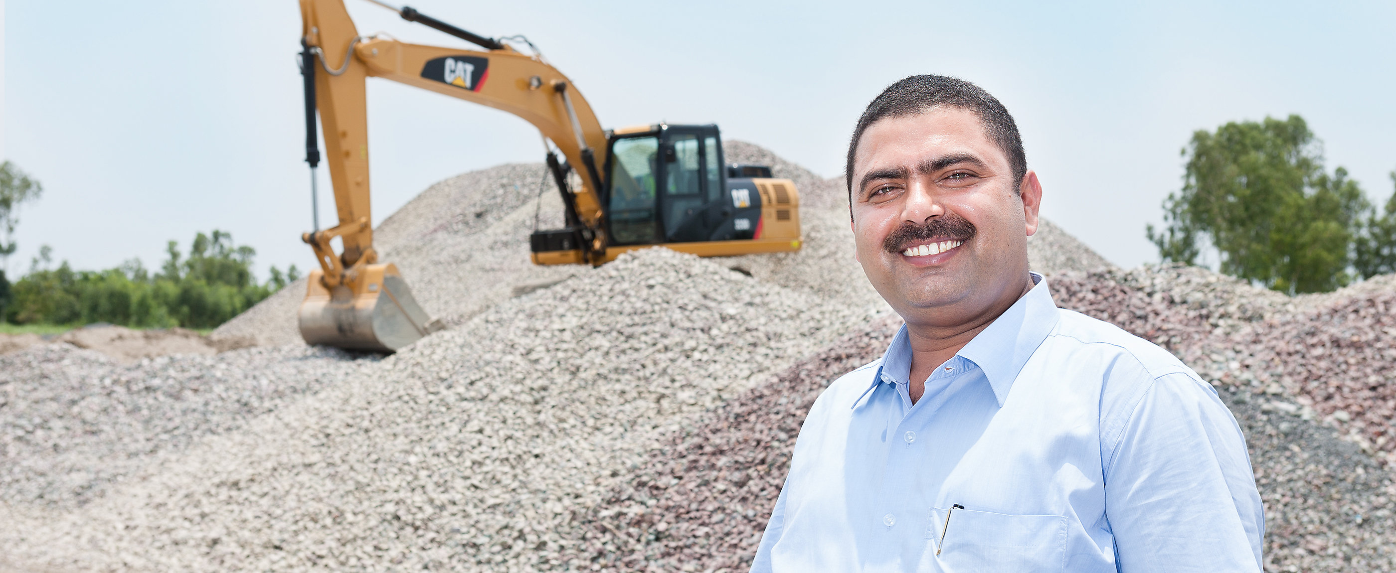 Male customer using Ipad with Excavator working in the background