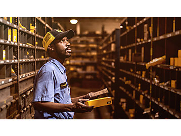 Dealer parts and service support team member finding parts