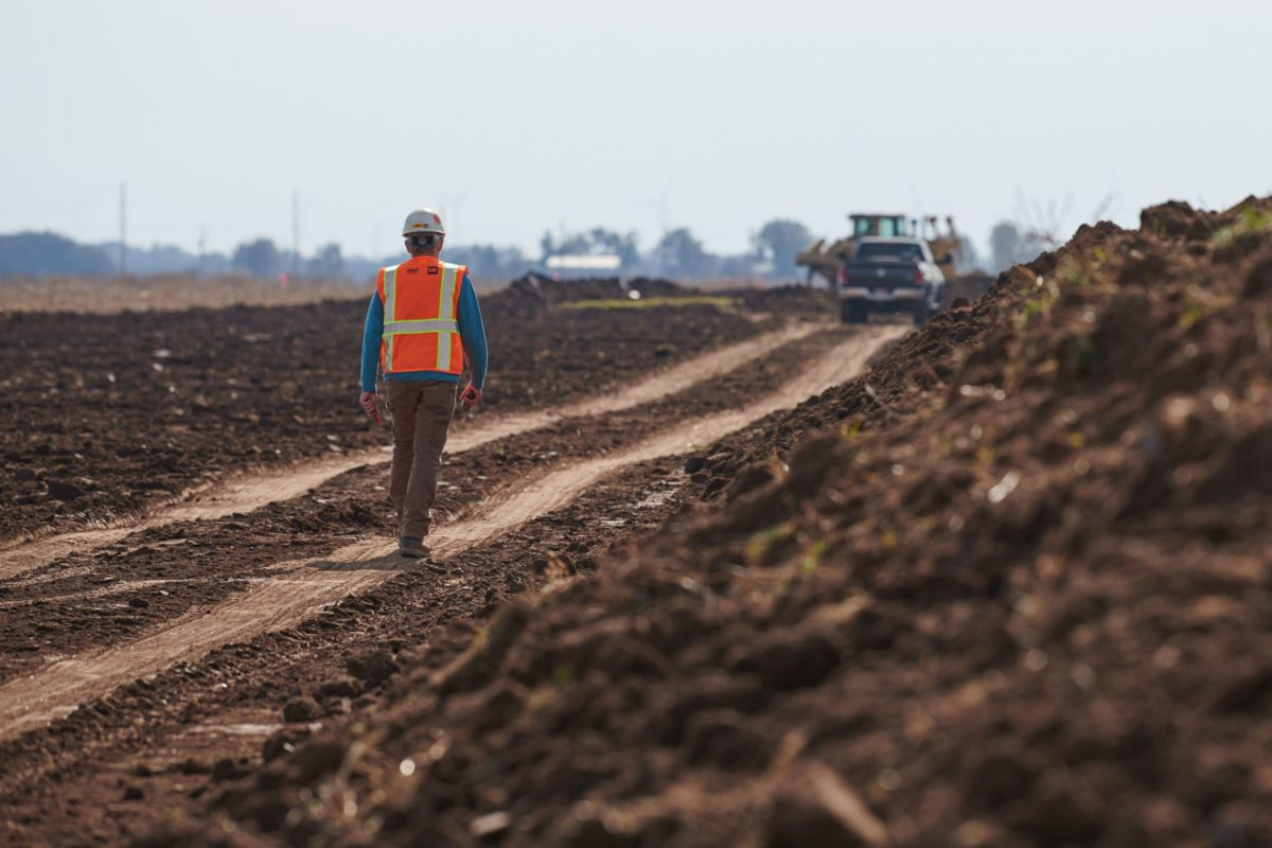 Operator walking on dirt road
