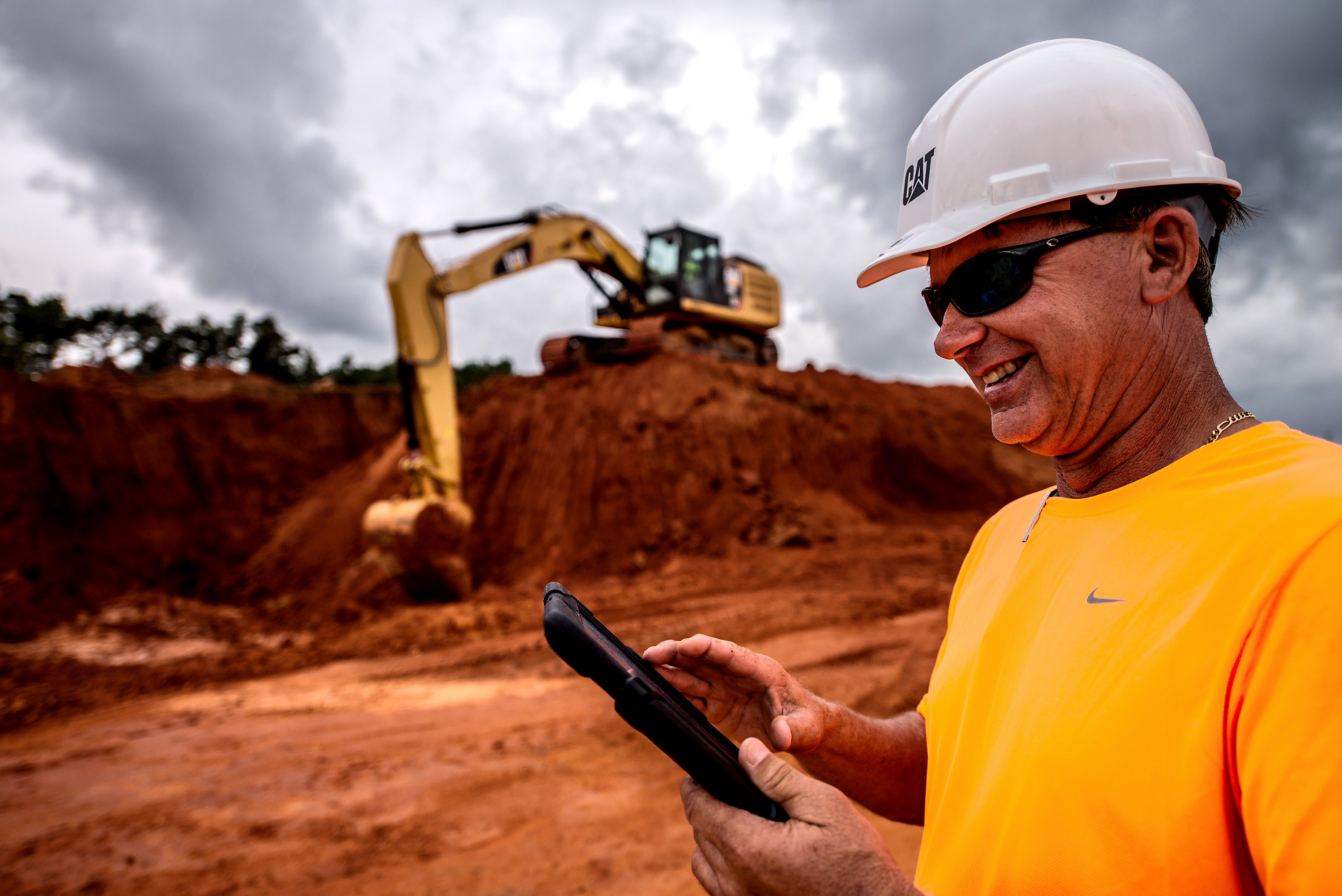 Customer using ipad on jobsite with excavator working in the background