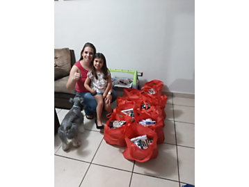 Regina and her daughter with the 10 bags of staple items they packaged up.