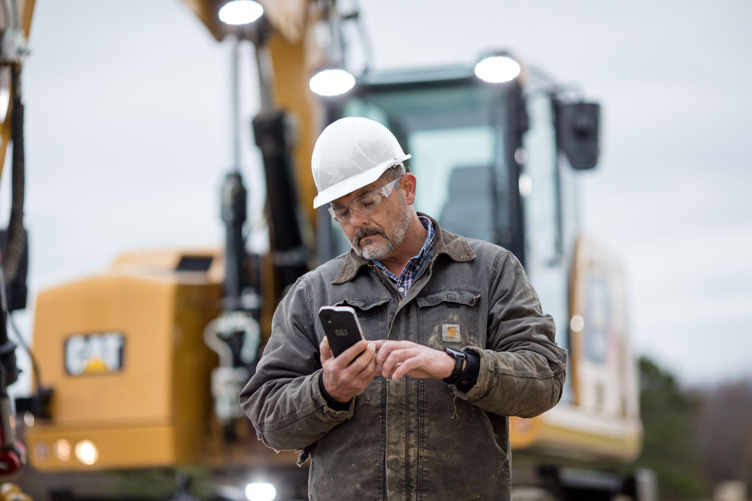 Man looking at phone at jobsite