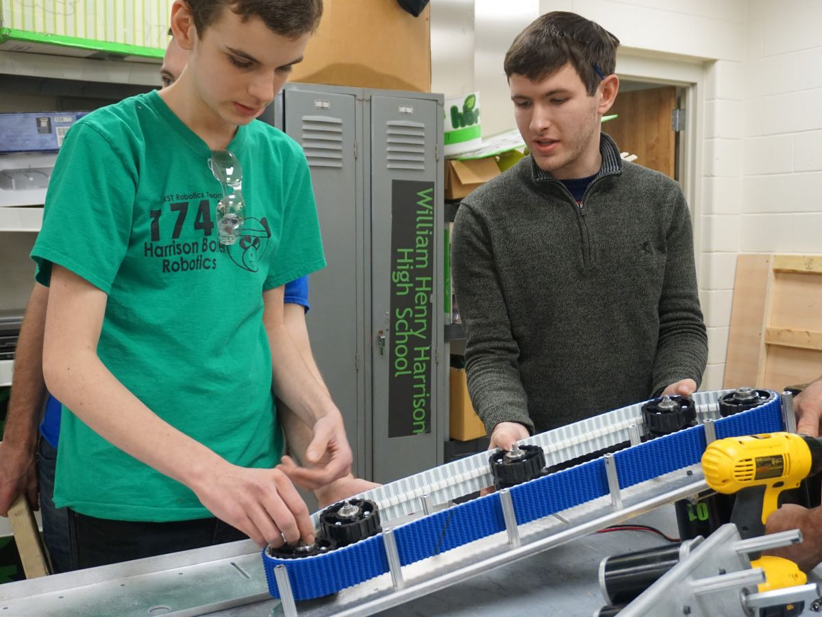 2 boys working on a robot