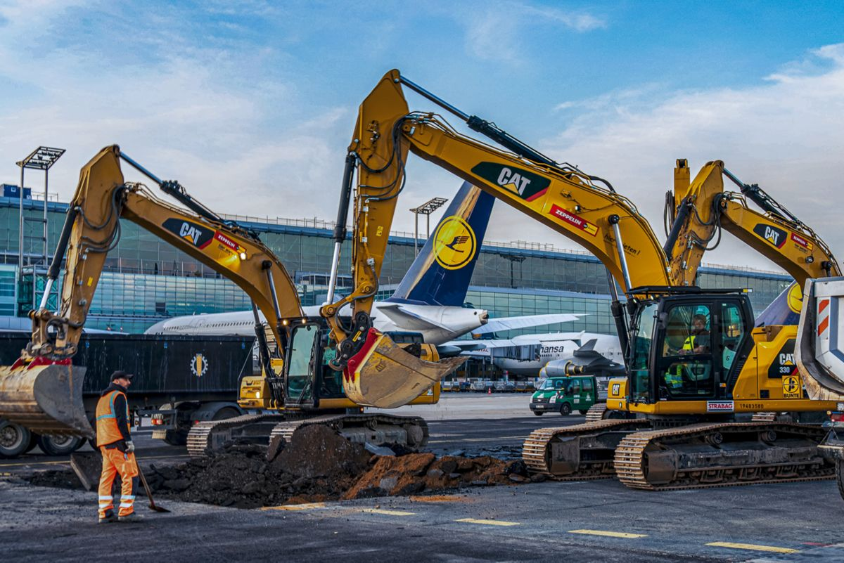 Four Cat 336 excavators hammer against the backdrop of Frankfurt Airport. Cat SmartBoom intelligent technology reduces vibration and loss of power.