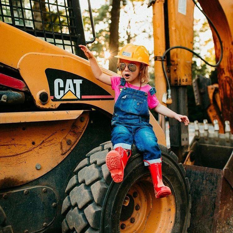 girl on excavator tire