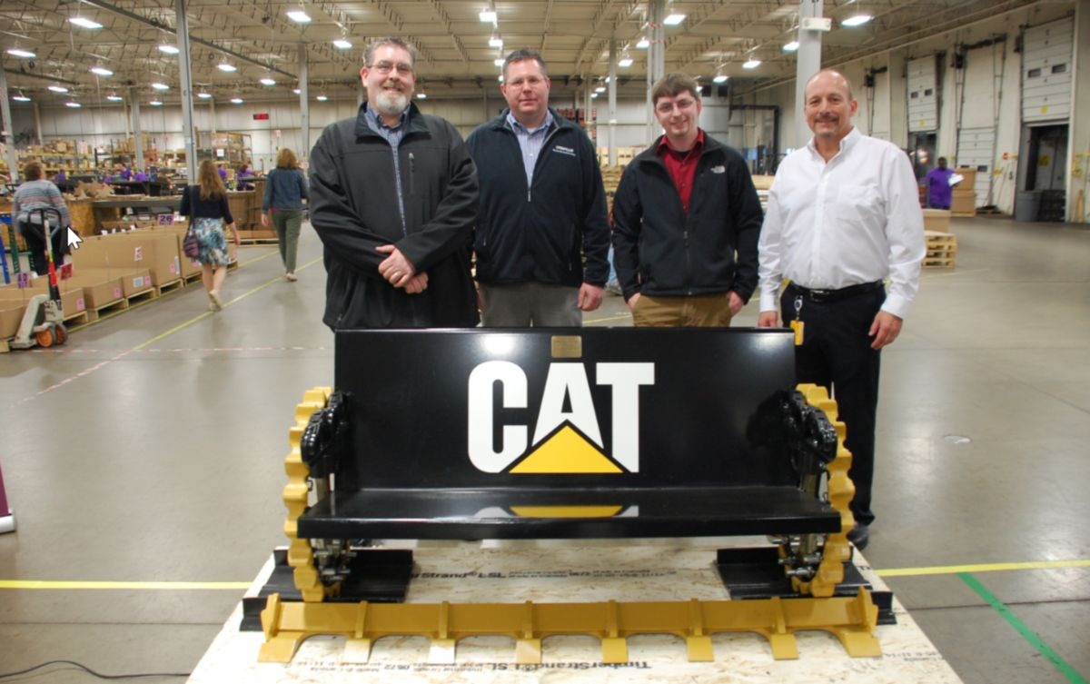 Caterpillar employees present a bench made of Caterpillar parts to the team at Peoria Production Shop.