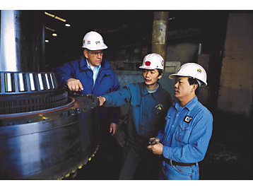 Cat dealer providing service at the An Tai Bao Mine, China, 2000.