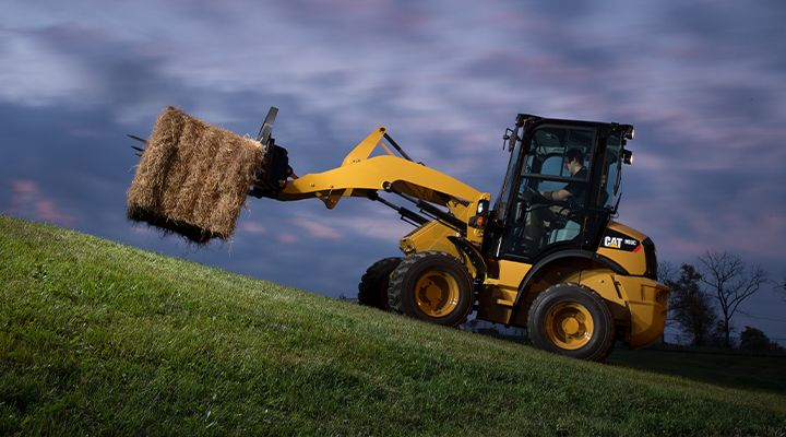 Man operating equipment moving hay with attachment