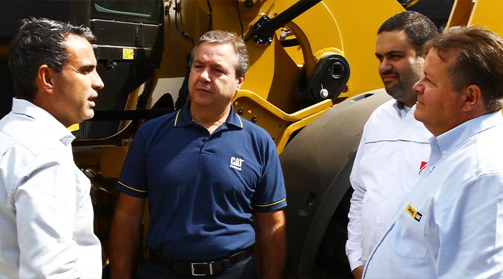 Three Cat employees talking next to equipment at a dealership