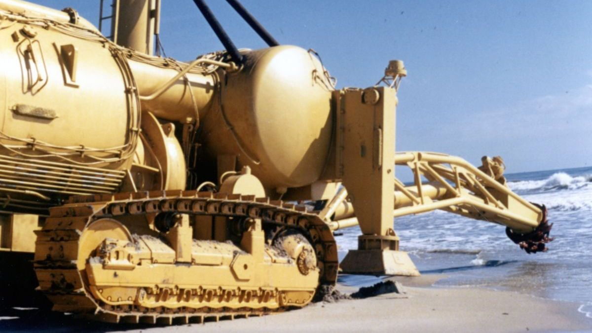 """""""Crawlcutter"""" underwater dredge with Cat® D9 track-type tractor tracks on a beach in California."""