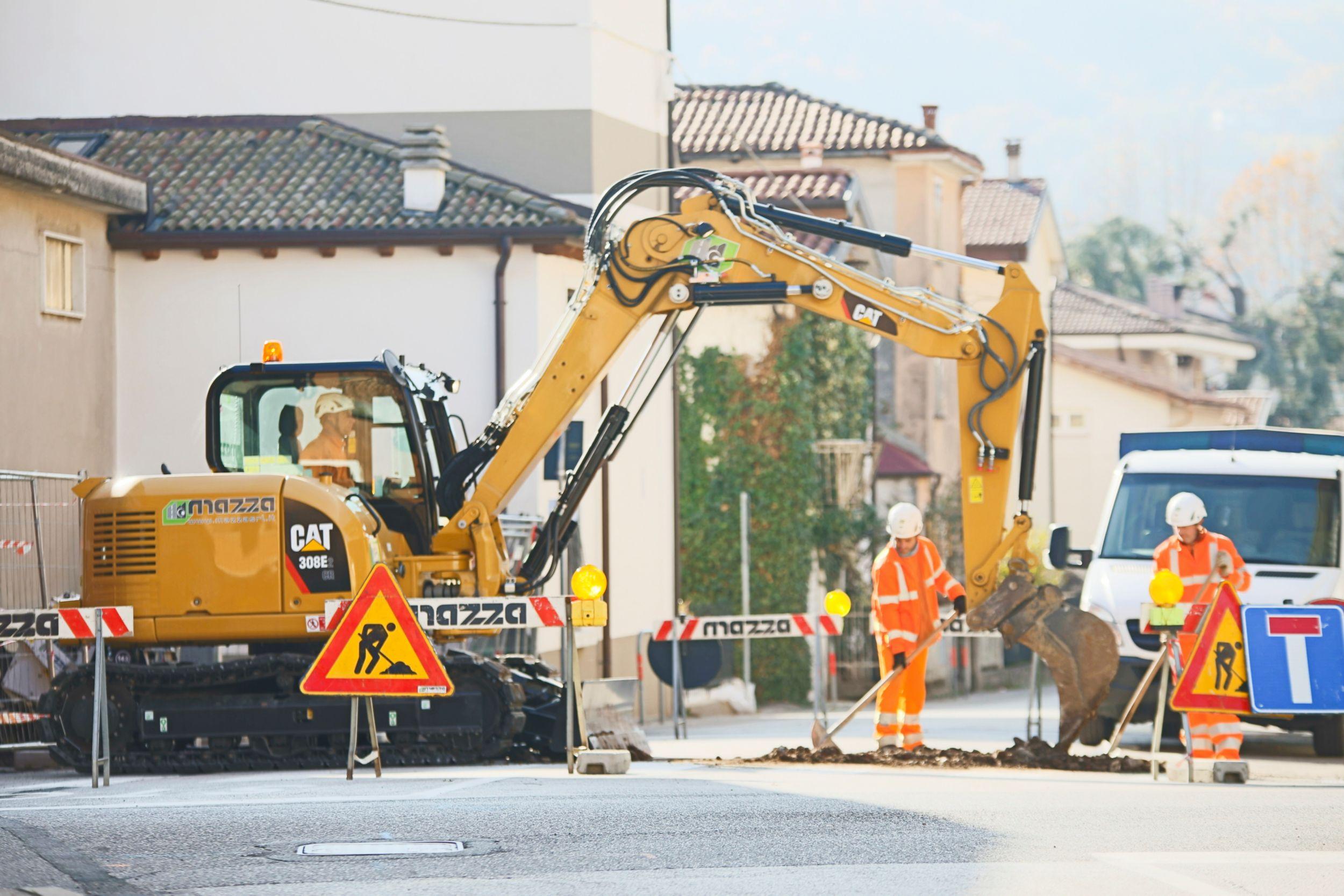Un cliente uomo che usa un iPad con un escavatore che lavora sullo sfondo