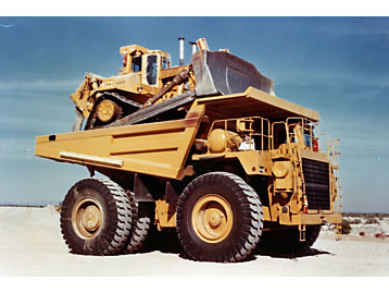 Cat D10 being hauled in the bucket of a Cat Off-Highway Truck.