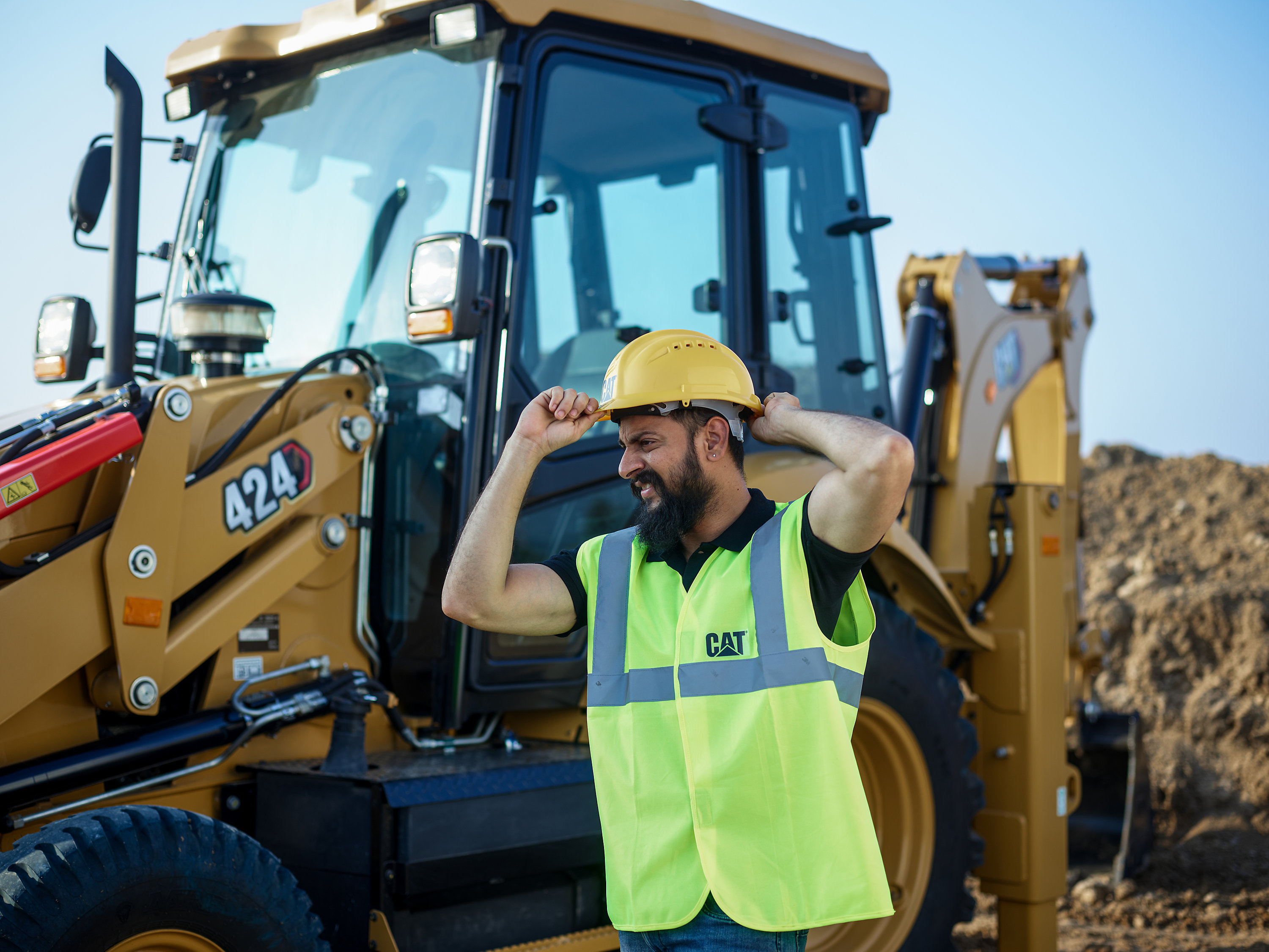 construction worker in a Cat hardhat on a jobsite