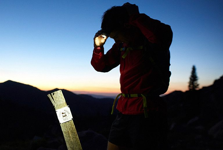 Trail Runner looking at trail marker with head lamp.