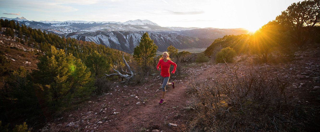 Woman running on a rocky trail with sun setting in the distance.