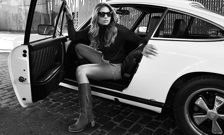 A stylish young woman in boots and sunglasses stepping out of a car.