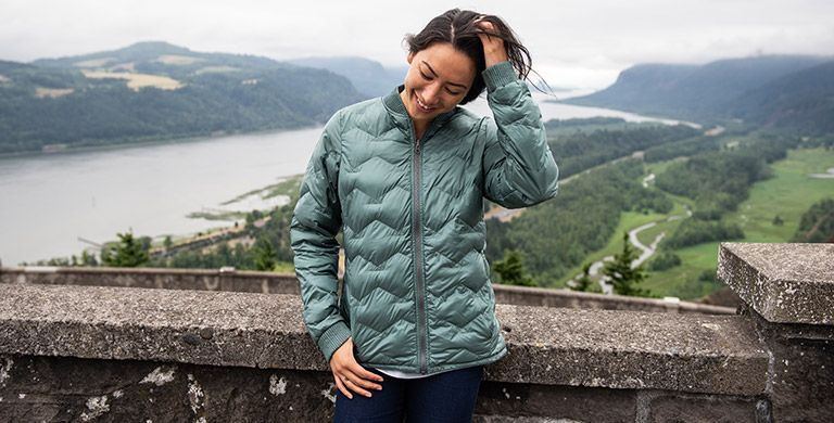 A woman in a puffy jacket overlooking a river gorge.