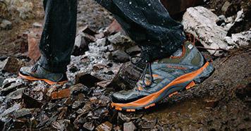Close-up of someone wearing Columbia trail shoes on rocky, wet terrain.