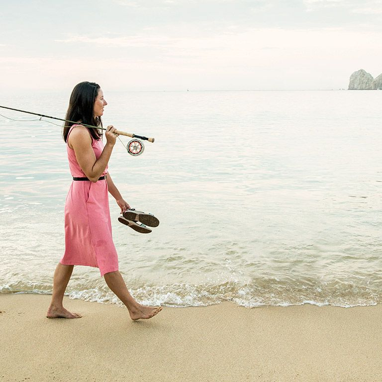 289d7bfefbcd A woman walking along a beach with a fishing rod.