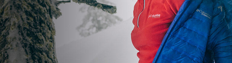 A woman wearing a red insulated mid layer in an outdoor setting.