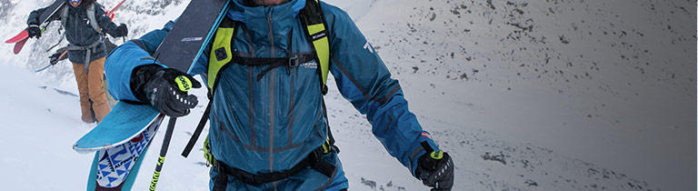 A skier wearing a blue OutDry Ex Mogul Jacket outer layer.