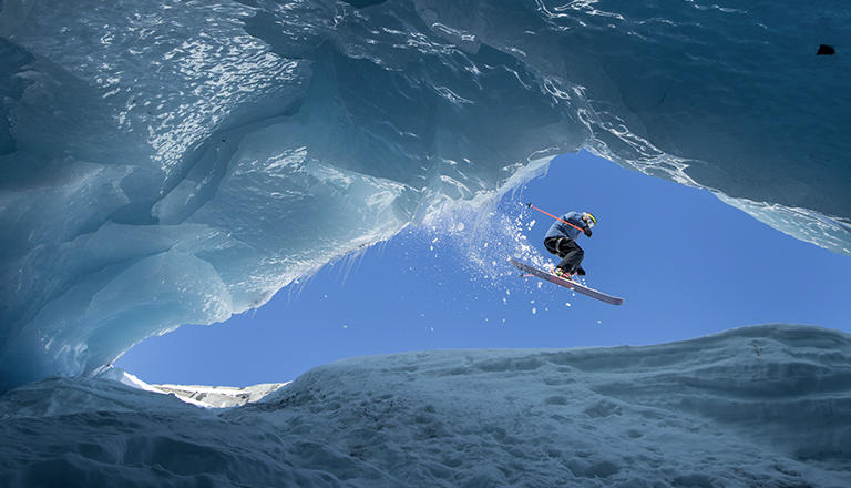 A skier jumping over a crevasse in Alaska.