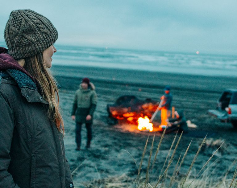 A woman in cold-weather gear looks out on a beach campfire and the ocean beyond.