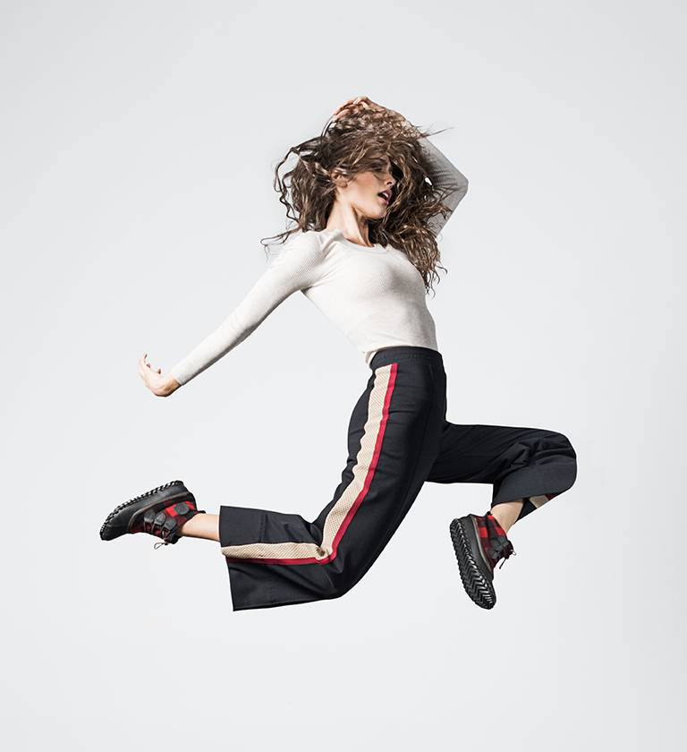 A young woman jumping in the air while wearing Out 'N About boots with a red and black buffalo check design.