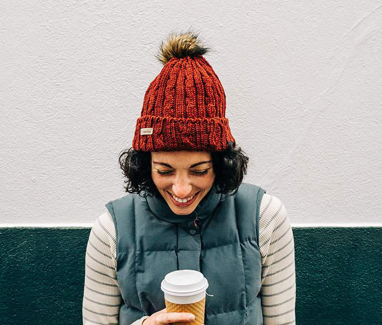 A woman in a red ski cap leans against a wall and laughs.