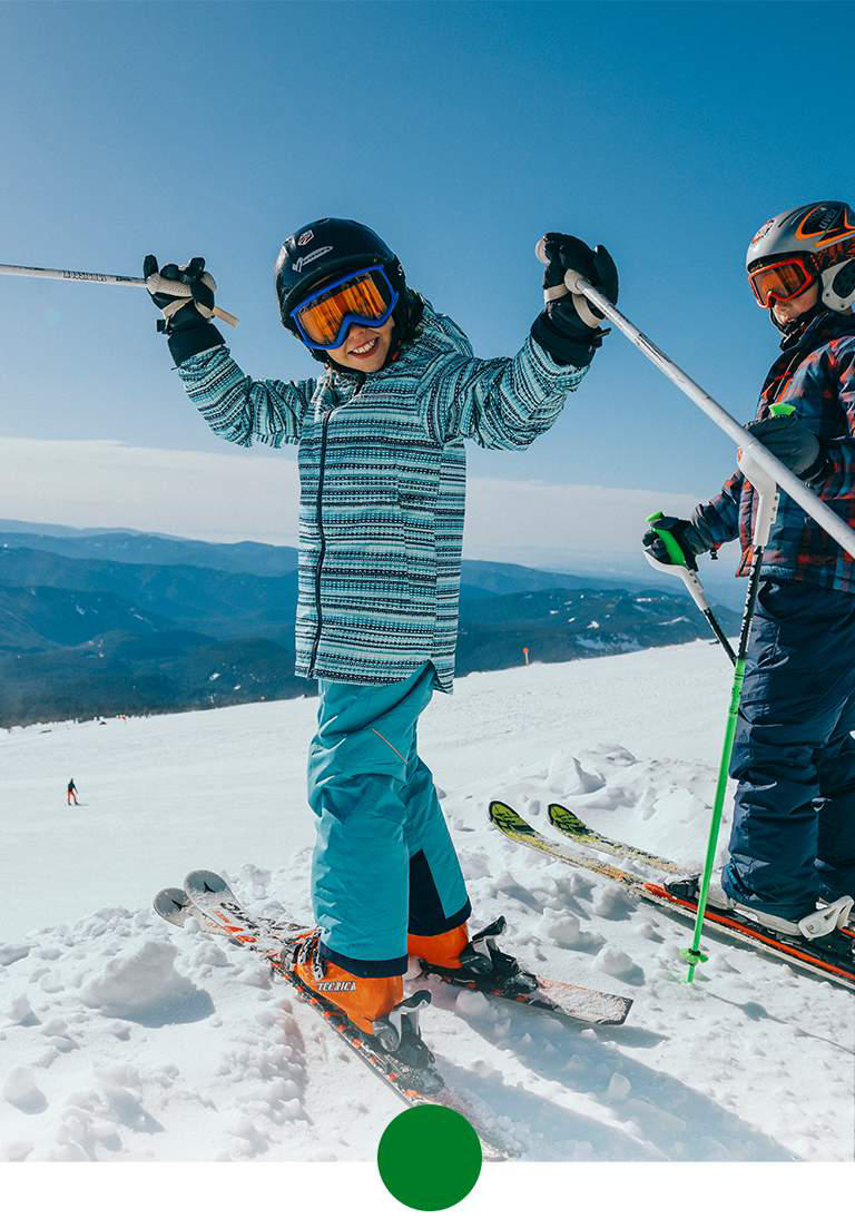 Two kids skiing in bright ski clothing.