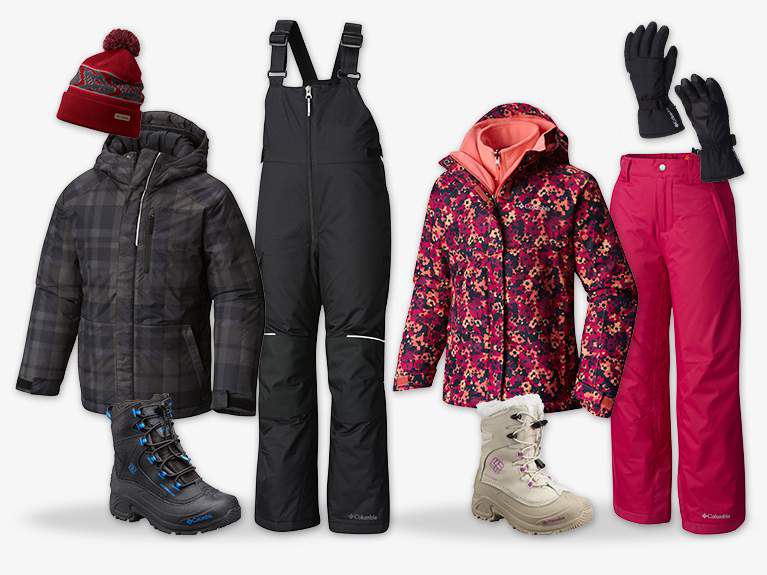 Close-up of multi-colored youth ski pants, jackets, hat, boots, and gloves.