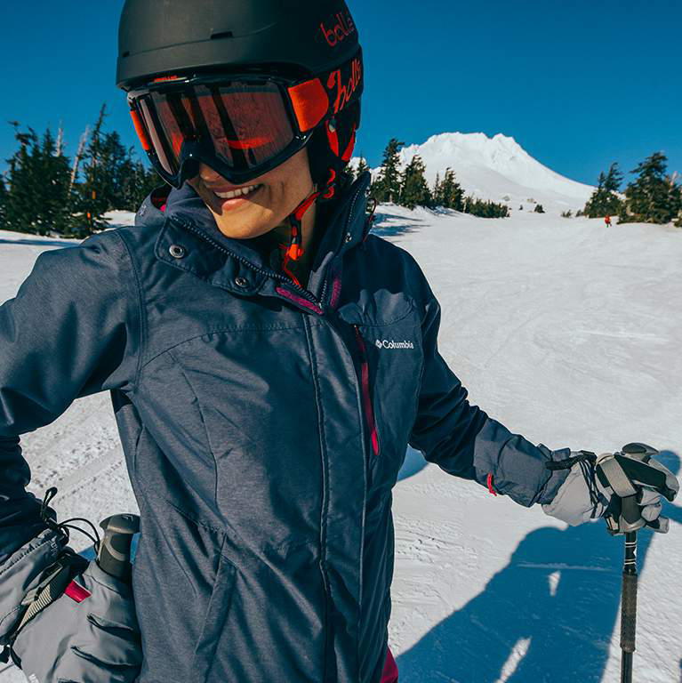 Close-up of a female skier in a blue jacket.