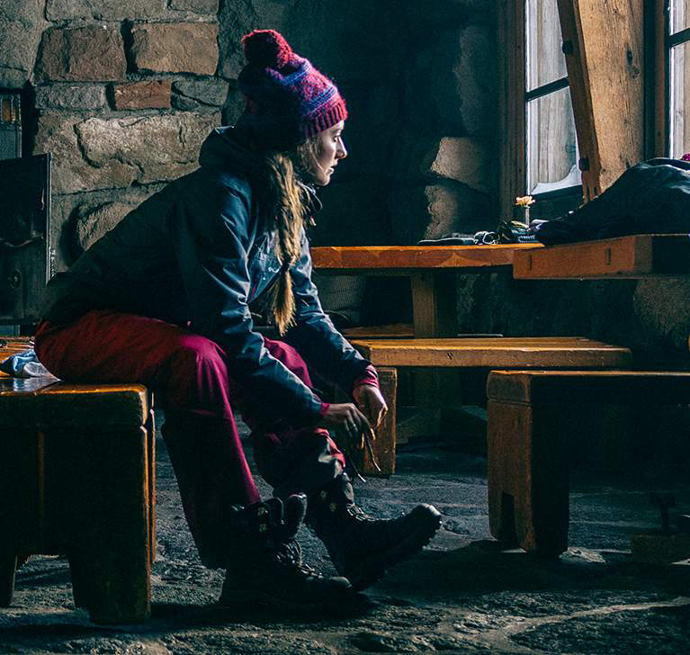 A woman sits on a bench in a ski lodge, lacing up her boots.