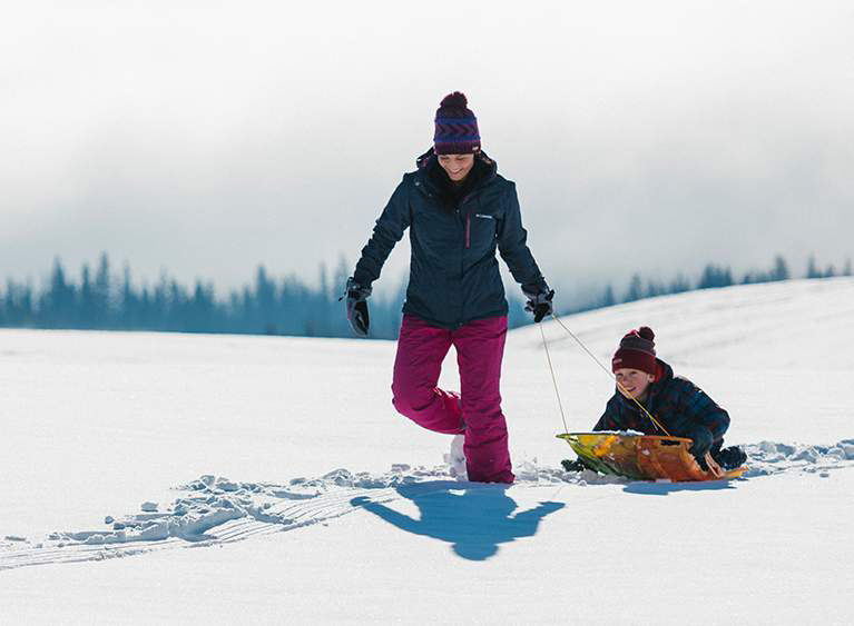 A woman in a blue ski jacket and purple ski pants pulls a child through the snow on a sled.