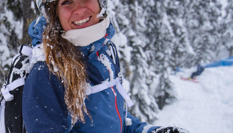 A smiling young woman in the snow.