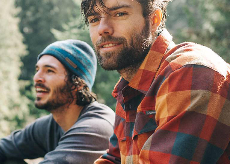Two young men in flannel shirts, tees, and caps.