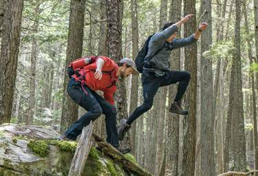 Zac and Dylan jumping over a log in the woods.