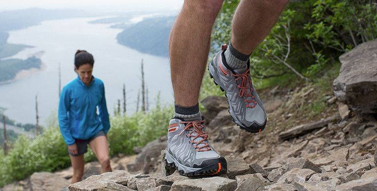 Image of men's hiking shoes with woman in background hiking up a trail.