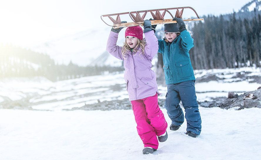 A girl and boy sledding in Columbia gear.