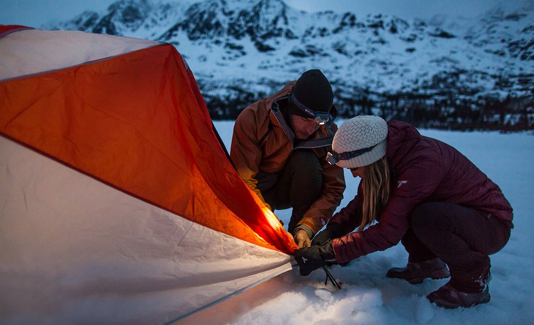 Justin and Chrishell Hartley tie down their tent on an Alaskan glacier.